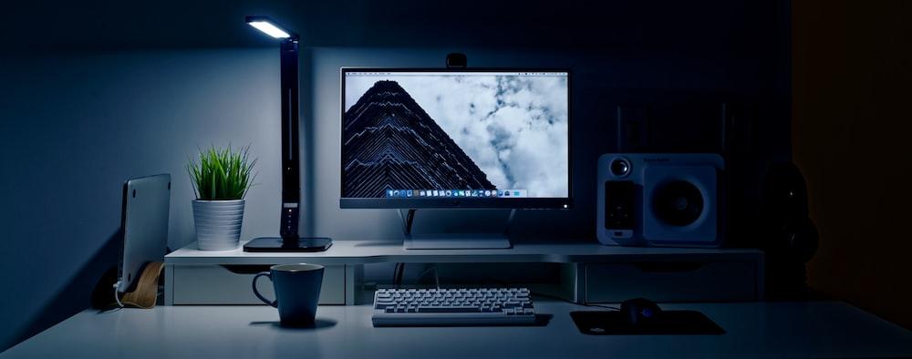 flat screen TV turned-on near keyboard, multimedia speaker, and ceramic mug on table