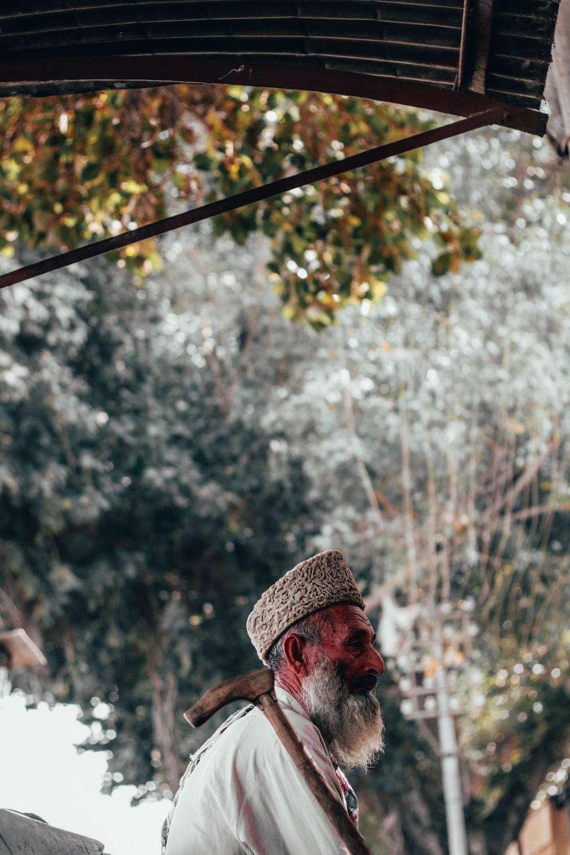man wearing white thobe robe and taqiyah hat