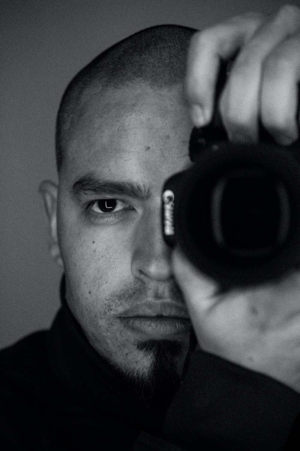 grayscale photography of man holding Canon camera