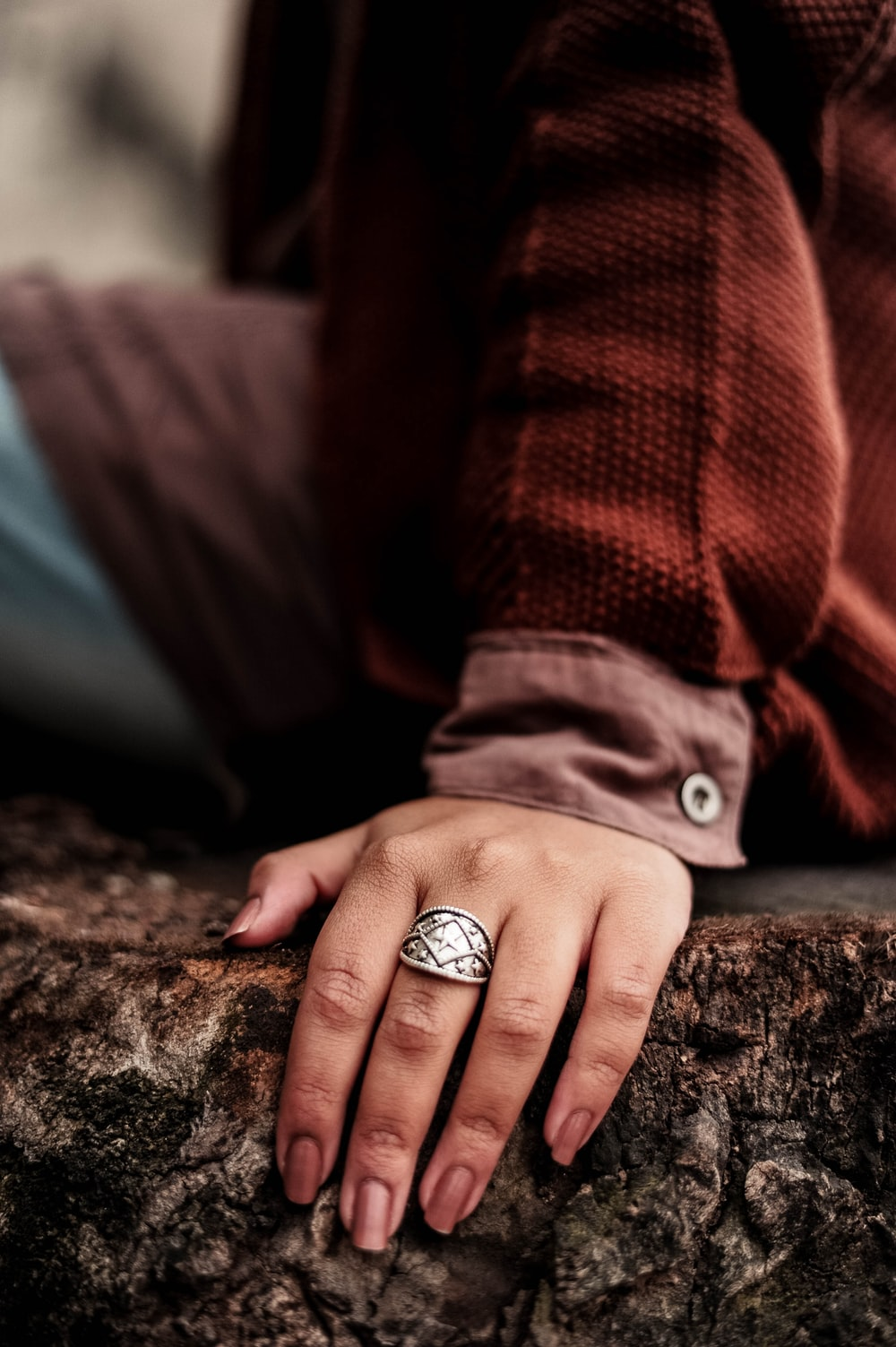 person sitting on brown tree trunk wearing silver-colored ring close-up photography