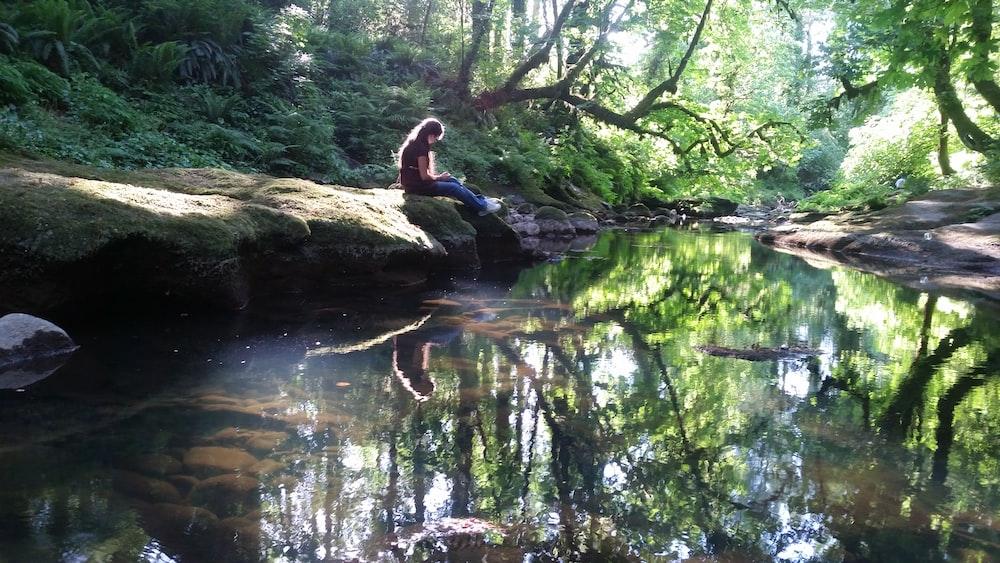 woman sitting beside body of water