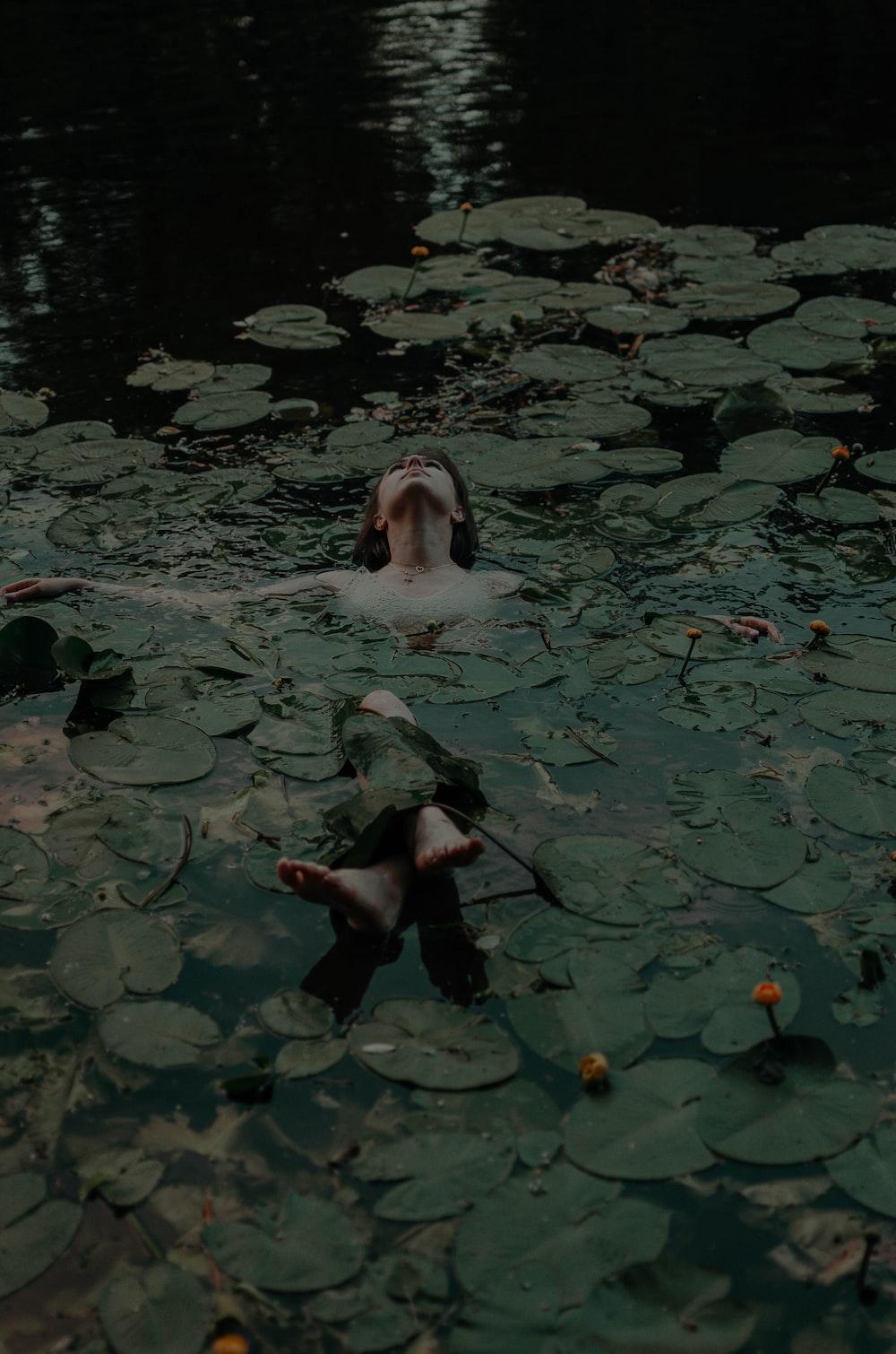 woman lying on body of water