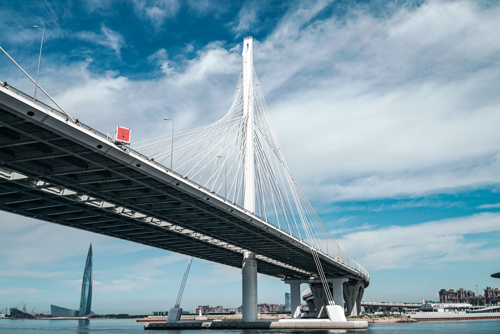 white bridge under white clouds and blue sky during daytime