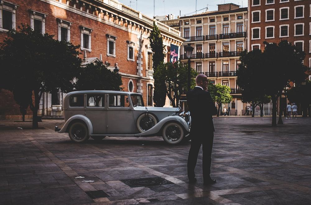 man standing near white vehicle
