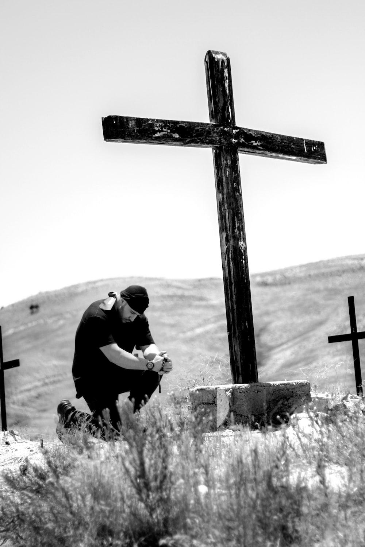 man kneeling in front of wooden cross