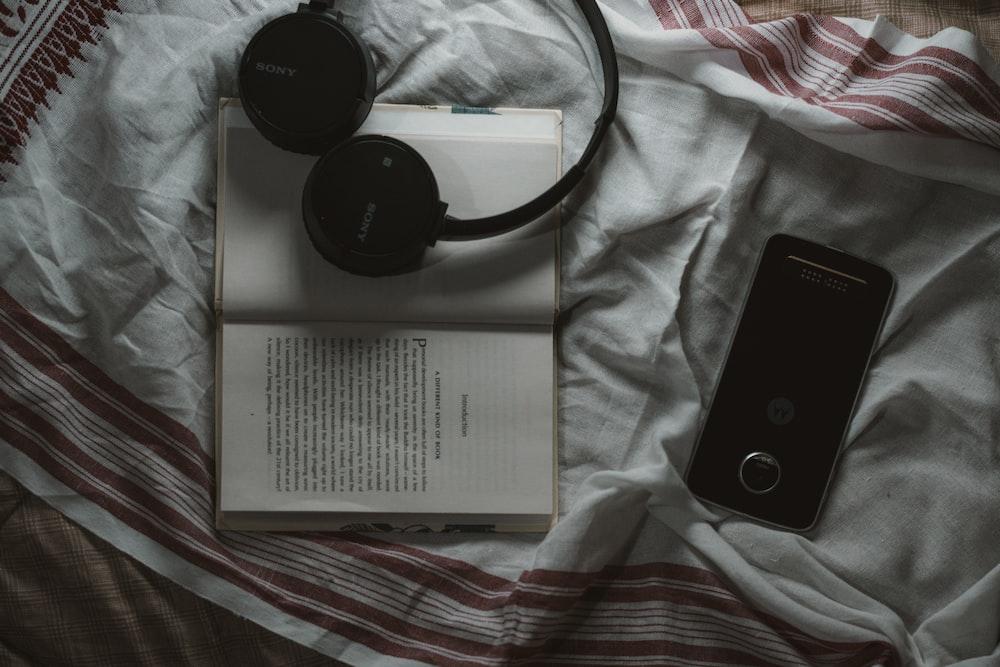 black Sony wireless headphone on top of white book