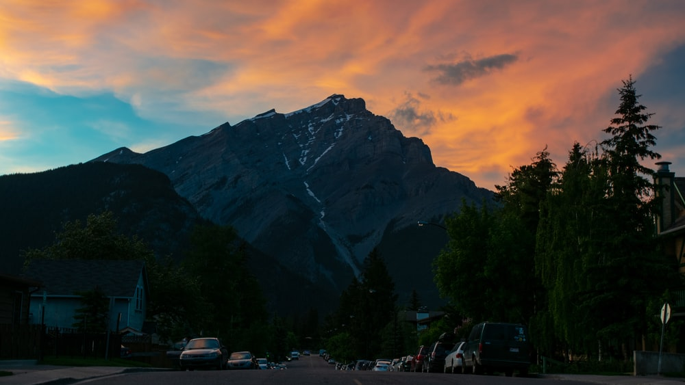 cars in street with snow capped mountain in background under orange sunset sky