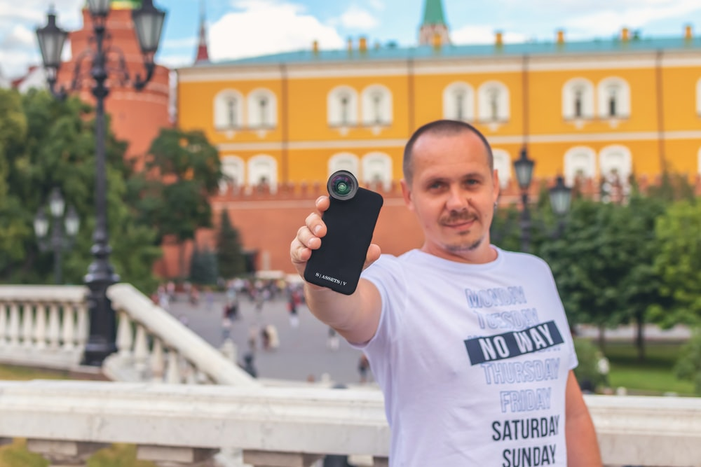 man wearing white and black crew-neck t-shirt standing and showing phone with fish eye lens