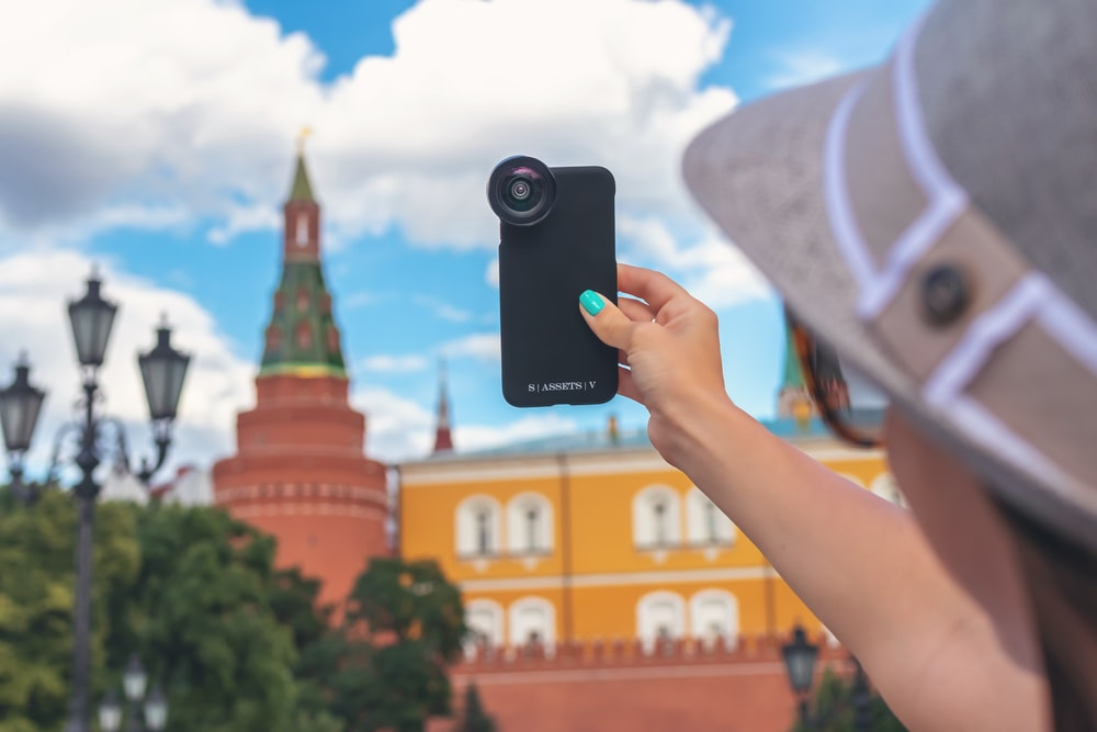 woman holding phone while taking picture
