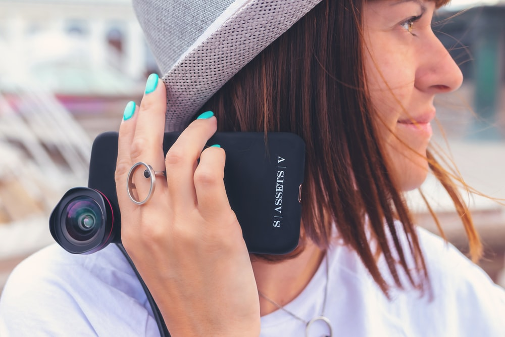 woman wearing white shirt and gray hat holding phone