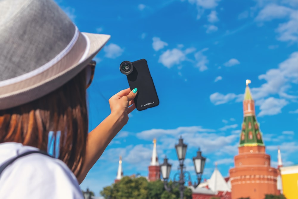 woman taking self portrait with clip-on zoom lens in smartphone