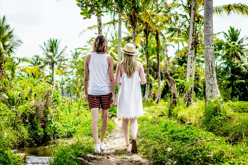 man and woman in white walking through a pathway