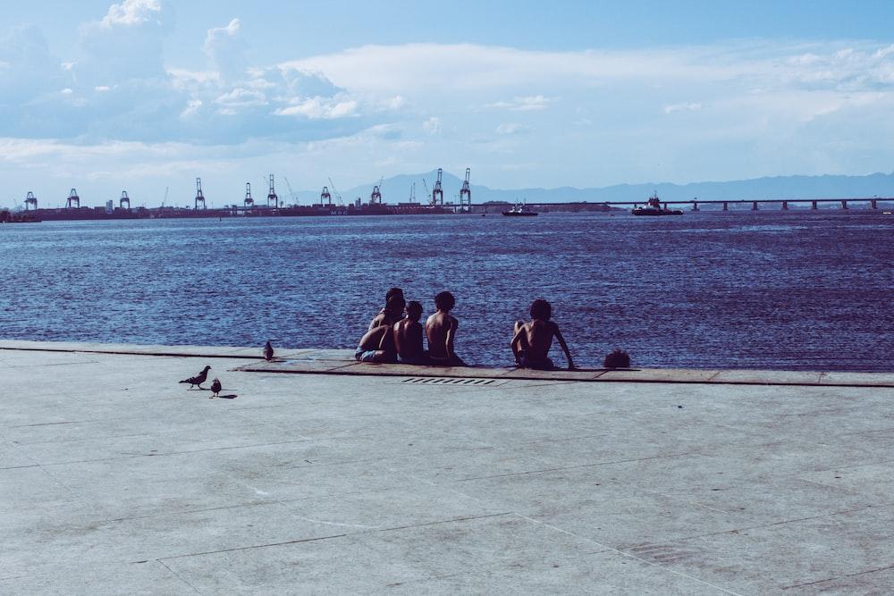 group of people sitting on sea dock