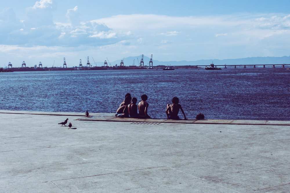 group of people sitting on sea dock