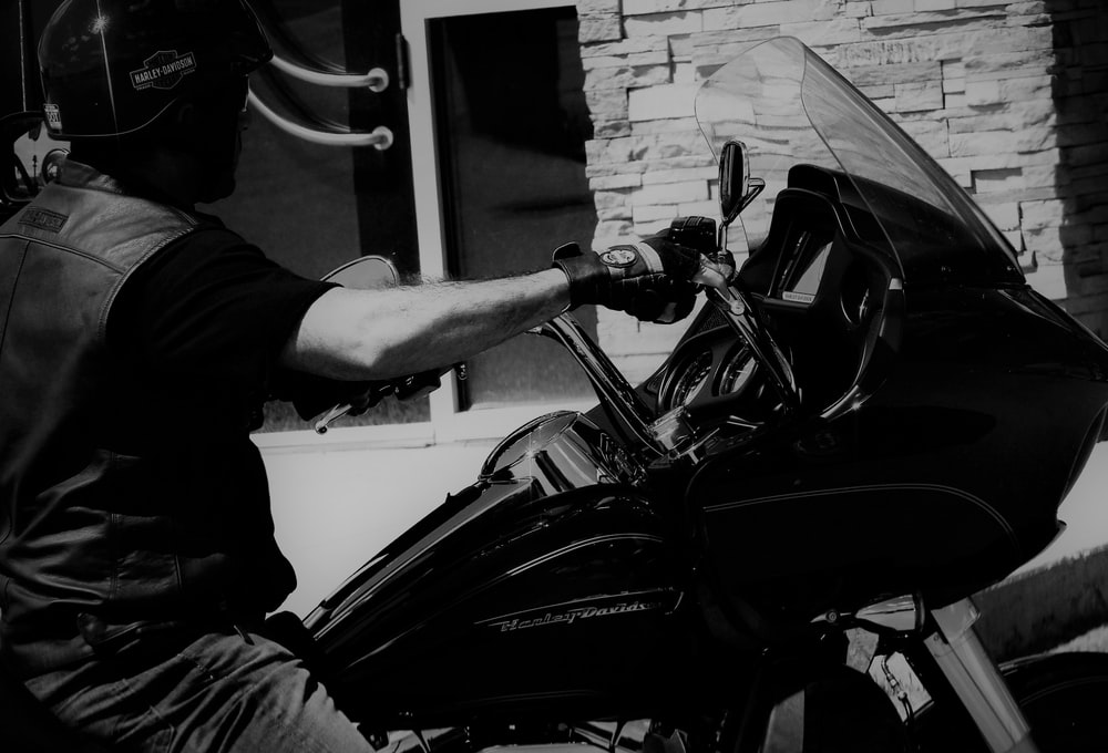 grayscale photography of man riding motorcycle