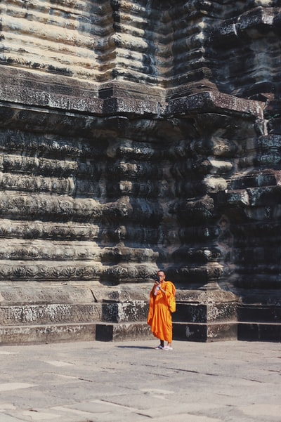 monk standing beside concrete building during daytime