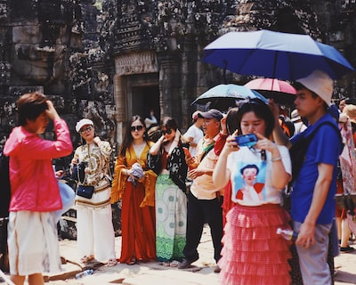 people standing in front of brown stone temple