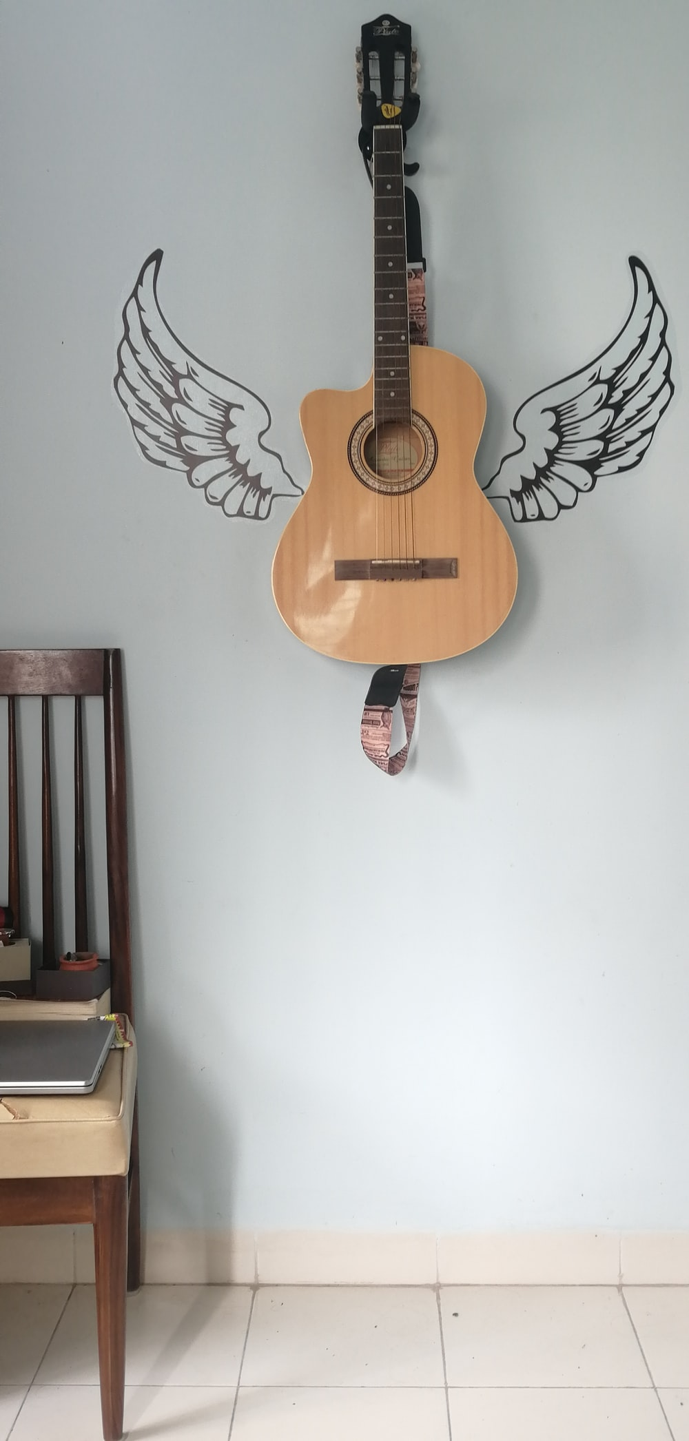 acoustic guitar hanging on wall with angel wings