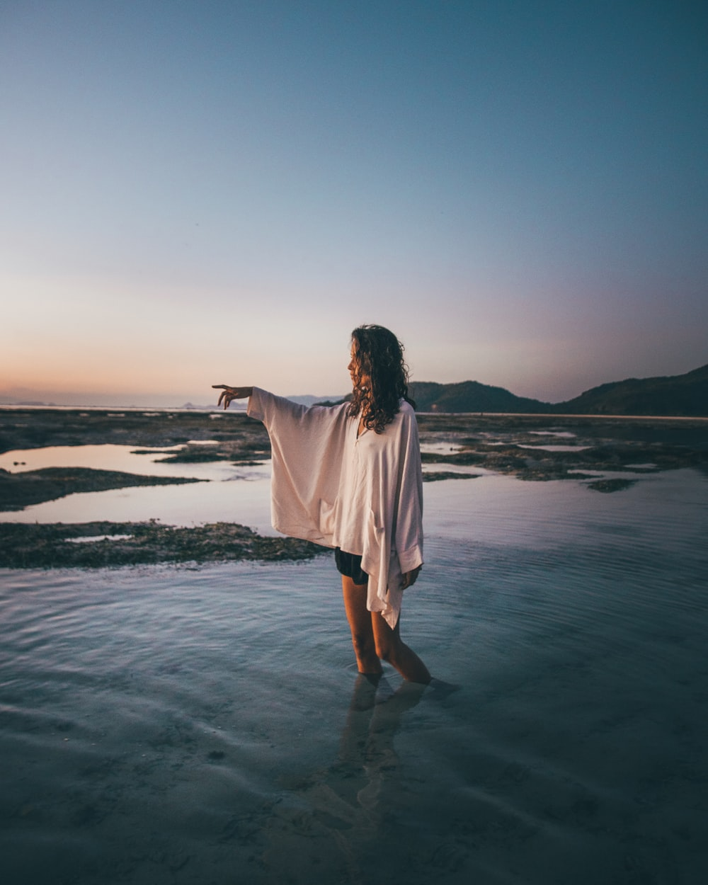 woman wearing white blouse standing on water