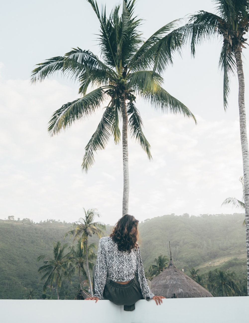 woman sitting on white surface near coconut tree