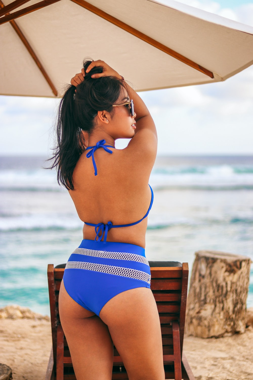 woman in blue and white bikini standing in beach