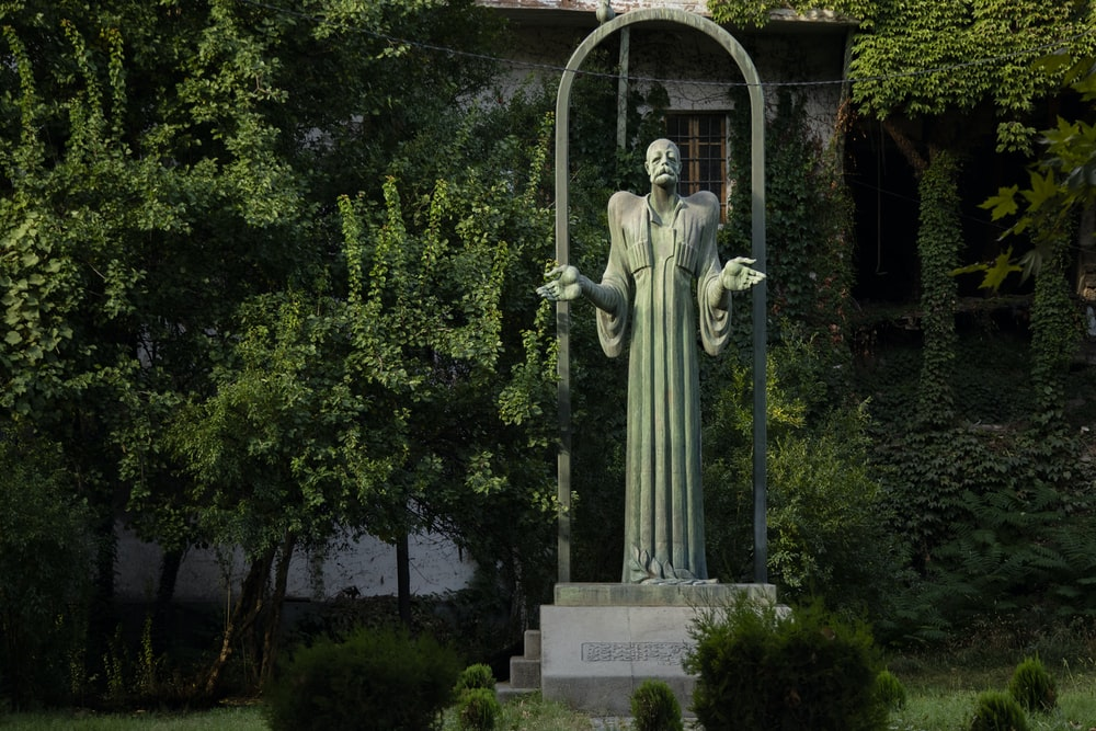 green statue in front of building covered with plants