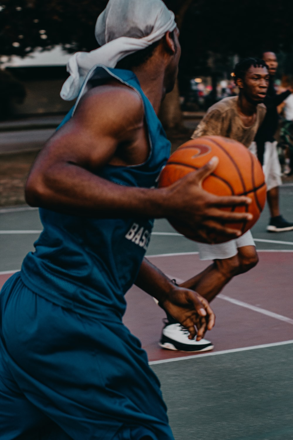 man in blue basketball uniform with ball in court