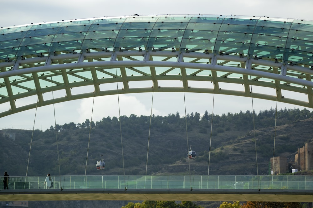 two people walking on green glass covered walk bridge