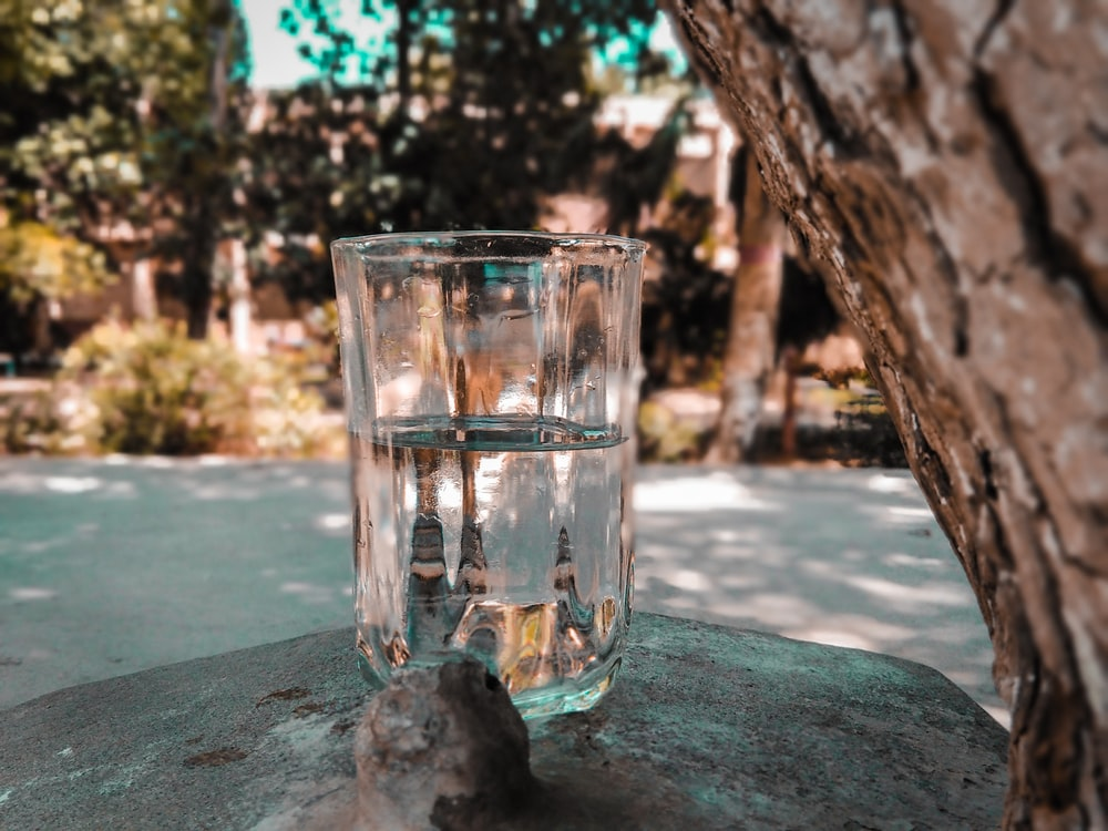 water in clear glass cup on grey rock