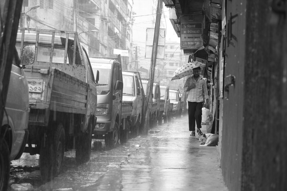 person walking in the rain holding umbrella beside parked vehicles