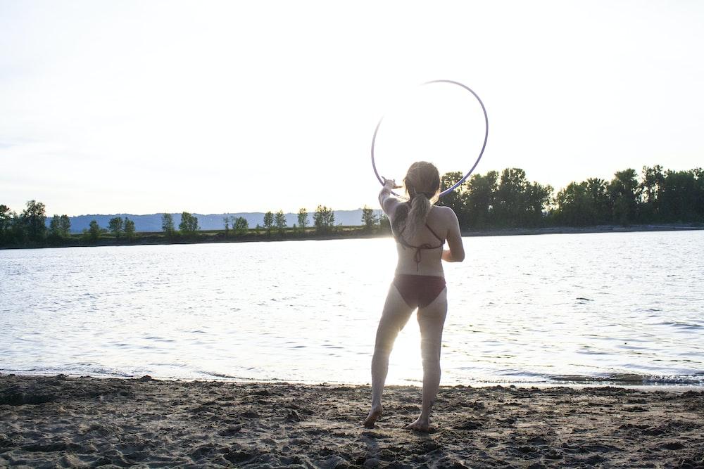 woman wearing brown bikini holding hula hoop standing on seashore