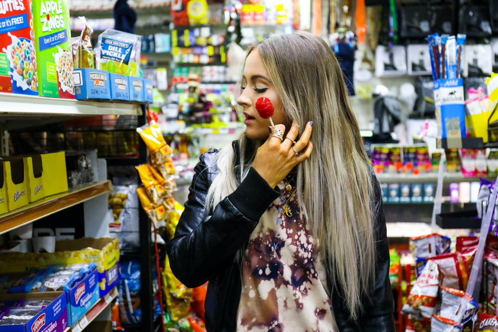 woman holding a red lollipop