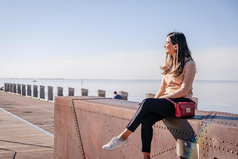 sitting woman wearing pink sweater and black leggings during daytime