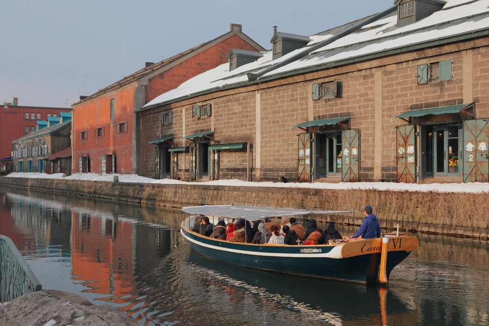 people riding on boat beside building