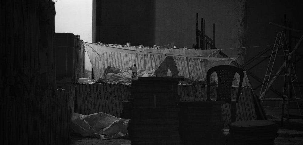 grayscale photography of person lying in bed with mosquito net