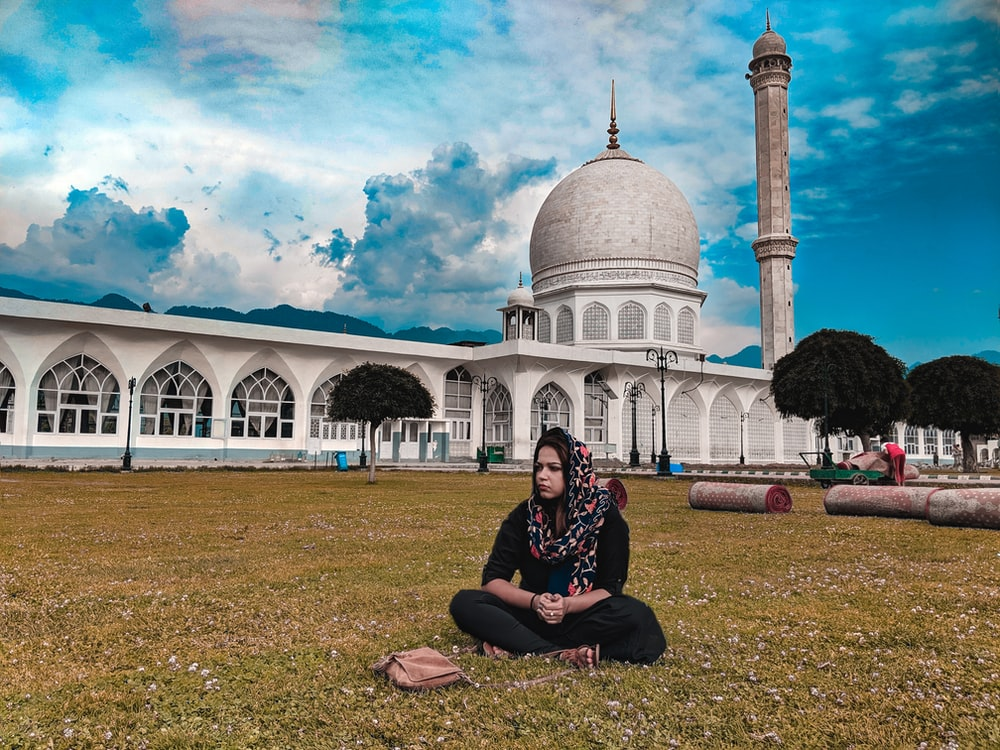 woman wearing gray hijab sitting in front of dome building