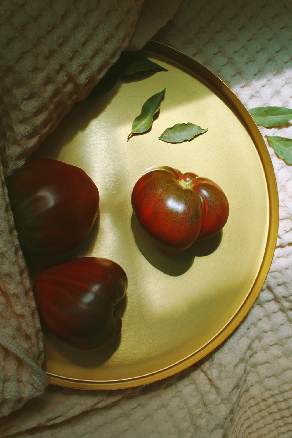 three red tomatoes on a gold tray