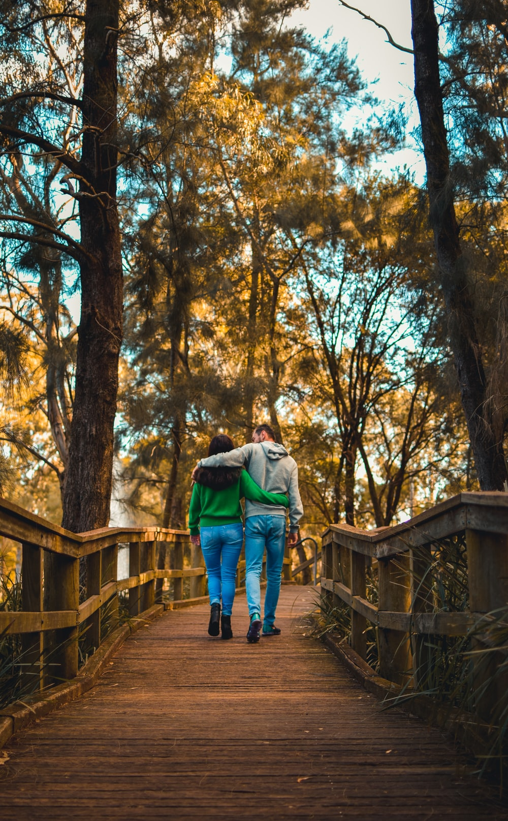 couple walking on pathway beside trees