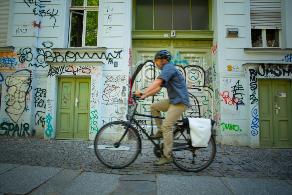 man riding bicycle beside graffiti building