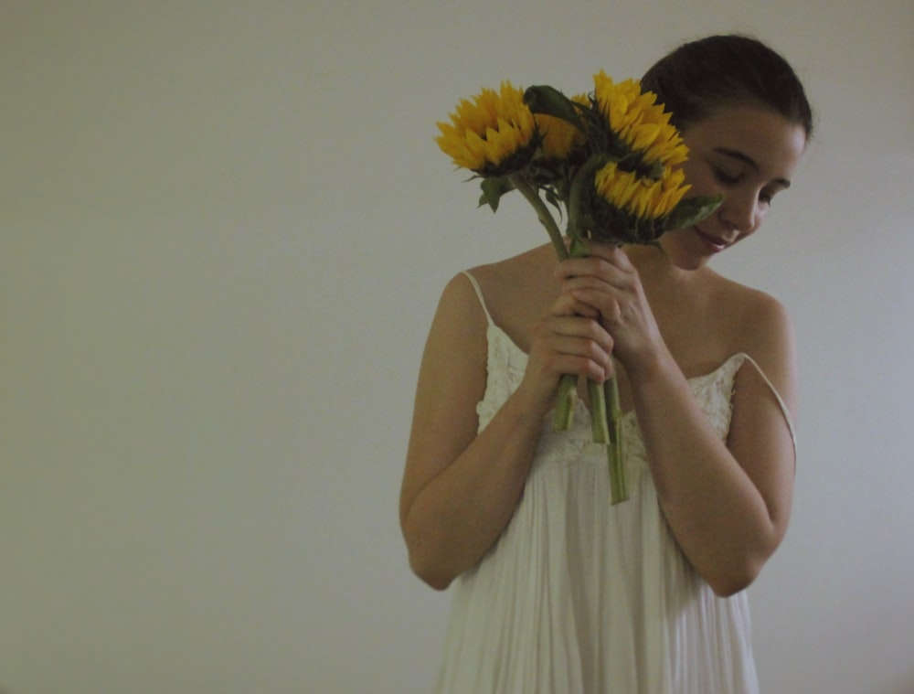 woman in white cami dress with bunch of yellow flowers