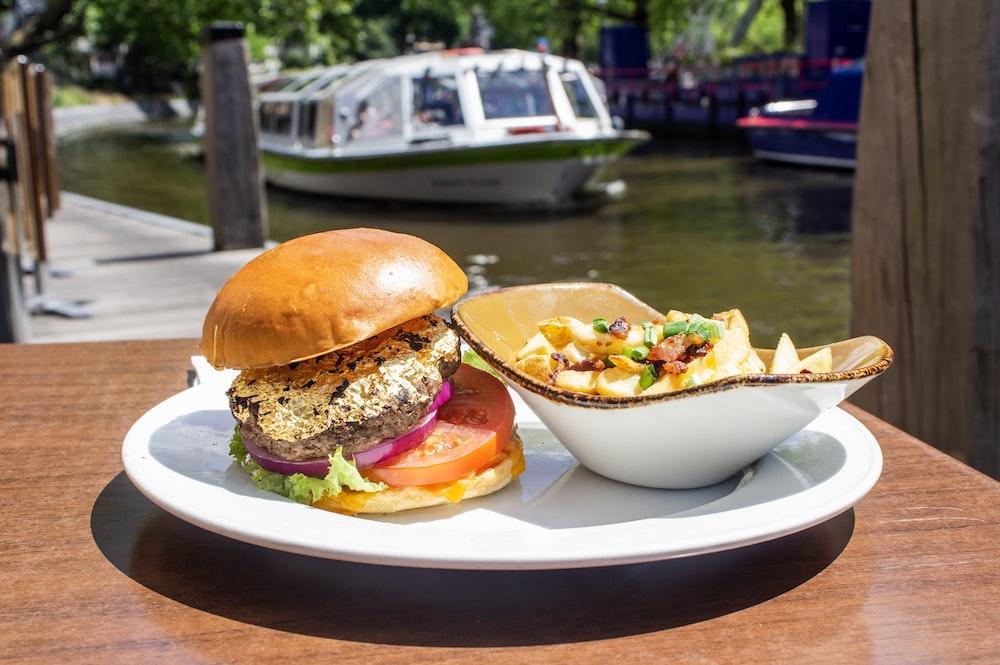hamburger and salad on white tray