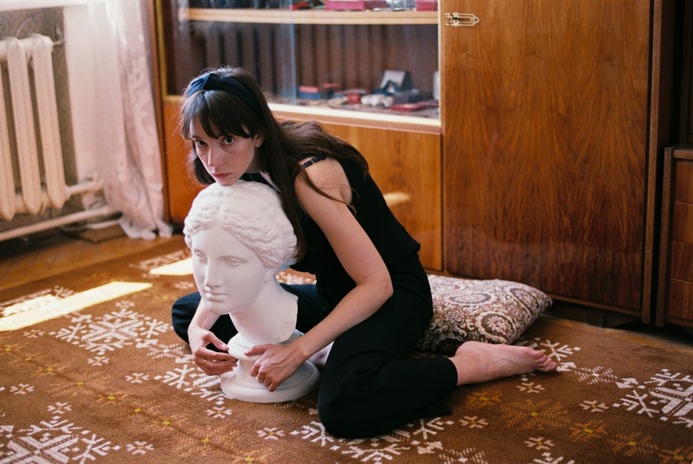 woman sitting on carpet hugging bust
