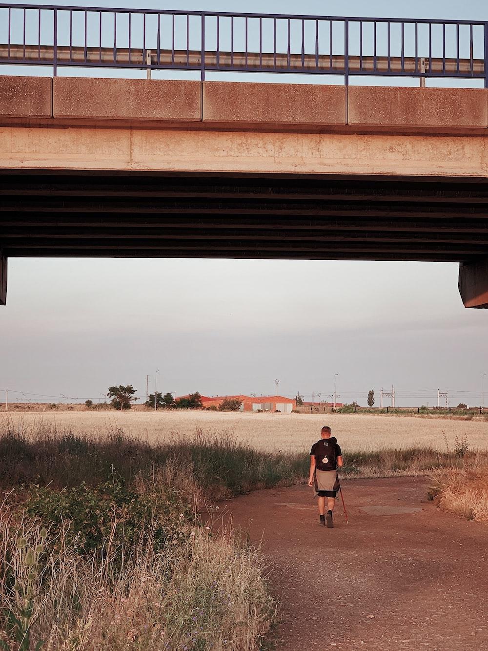 man walking on road under the bridge during daytime