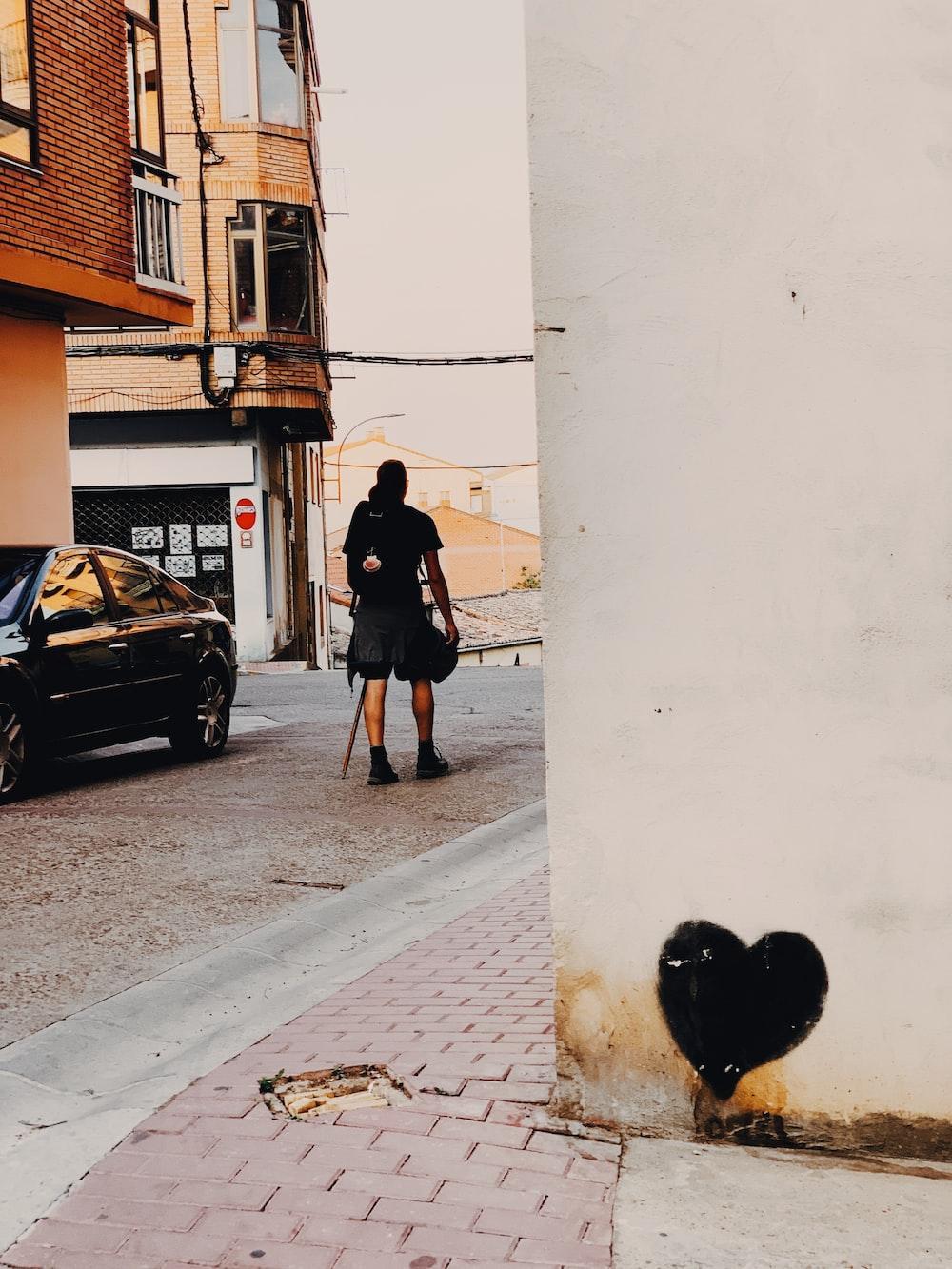 man walking on road passes by black car during daytime