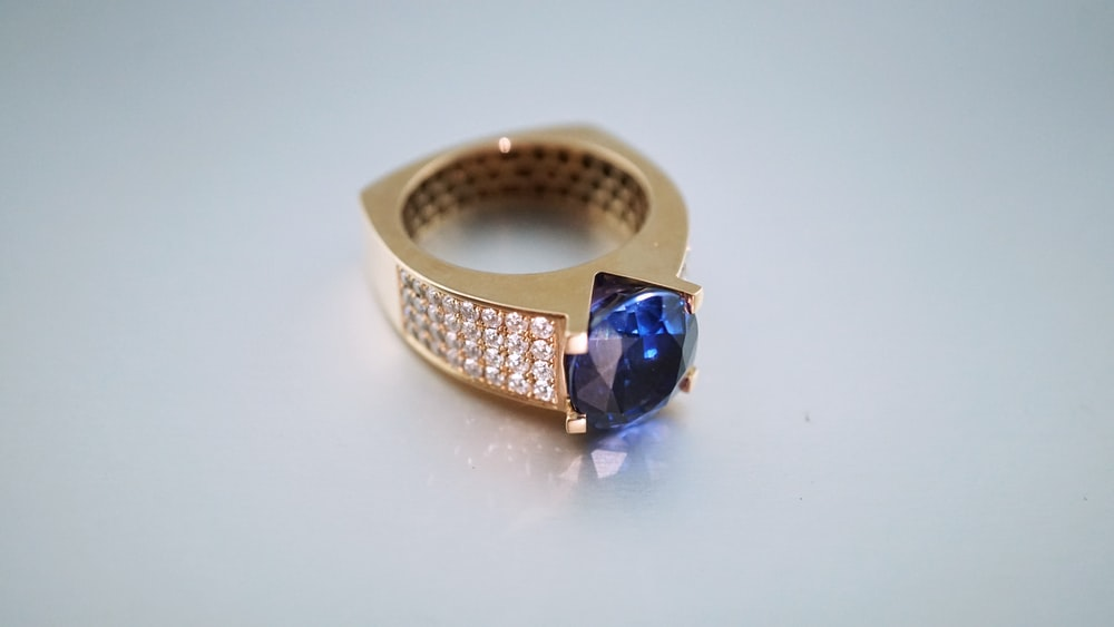gold-colored and blue gemstone ring