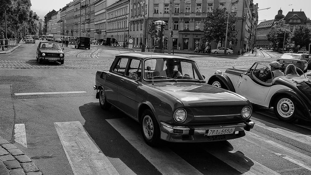 grayscale photo of classic cars in street