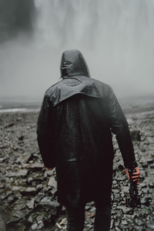 photography of man holding camera walking towards waterfalls during daytime