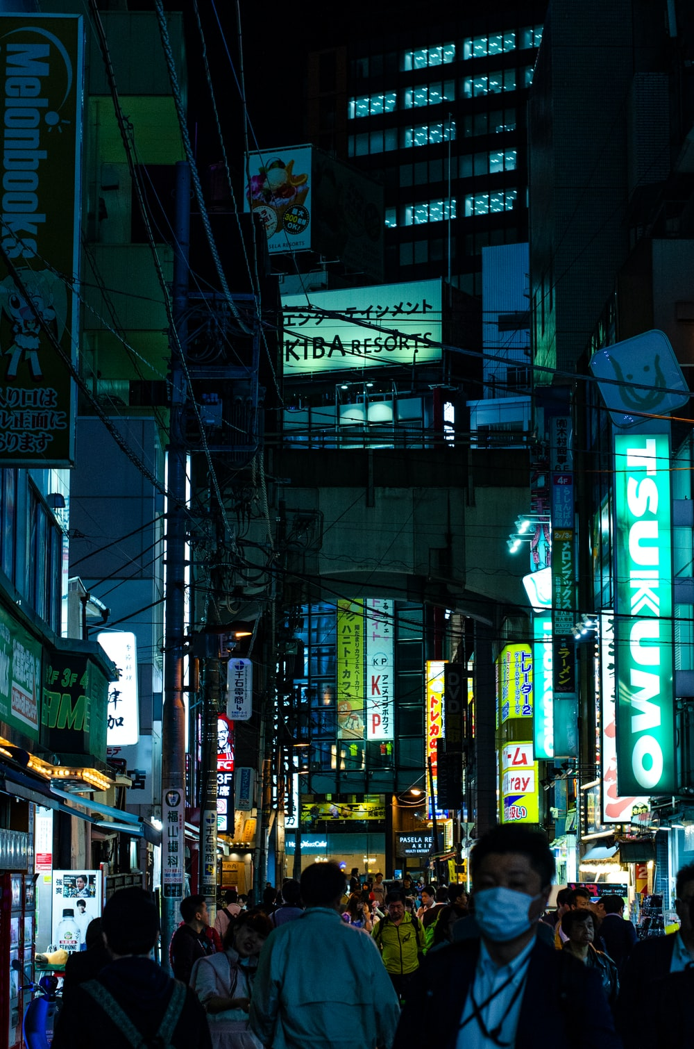 people gathering near street between building during nighttime