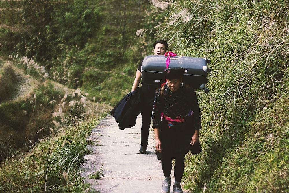 man walking behind another man carrying luggage bag