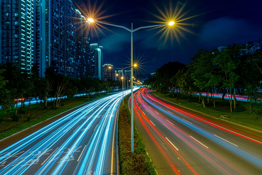 timelapse photography of vehicle tailights in street with lighted post beside buildings at daytime